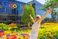 Tourist visit Google headquarters. Mountain View, California, USA - August 13, 2018: Smiling tourist woman on Google bike under Google sign at Google Stock Photography
