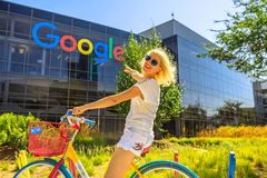 Tourist visit Google HQ. Mountain View, California, USA - August 13, 2018: Smiling woman on Google bike pointing Google sign at Googleplex Headquarters building Stock Photos