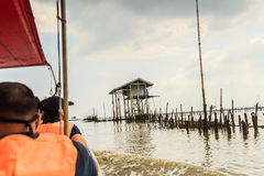 Tourist visiting the Hut in the sea that used for the owner to s. Hut in the sea that used for the owner to stay and guard his cockle farm in Samut Songkram Royalty Free Stock Photos