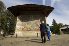 Tourist at Voronet monastery, Romania. Two tourists visit the Voronet monastery in a beautiful autumn day Stock Photos