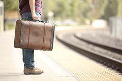 Tourist waiting in a train station. Casual traveler tourist waiting in a train station with a retro suitcase Stock Photos