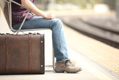 Tourist waiting in a train station. Casual traveler tourist waiting in a train station with a retro suitcase Royalty Free Stock Images