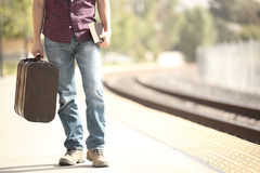 Tourist waiting in a train station. Casual traveler tourist waiting in a train station with a retro suitcase and a book Royalty Free Stock Photo