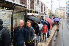 Tourist waiting for tram 28 in Lisbon, Portugal. Lisbon, Portugal - 5/10/2017: Tourists waiting in line for tram 28 under the rain Royalty Free Stock Photo