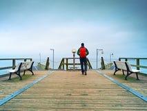 Tourist walk in autumn mist on wooden pier above sea. Rainy day Stock Photos