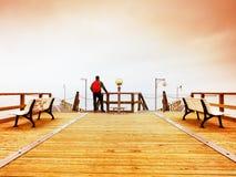 Tourist walk in autumn mist on wooden pier above sea. Rainy day Stock Images