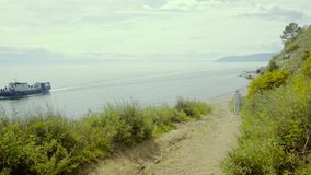 Tourist walkin on the country road near the Baikal lake. Path on the hill stock video