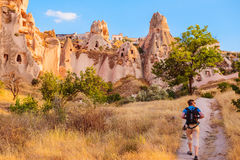 Tourist walking along cave rocks in Cappadocia Stock Photo