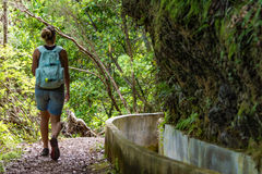 Tourist is walking along levada canal. Royalty Free Stock Photos