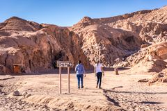 Tourist walking into Atacama`s Caverna de Sal salt cave attraction in Chile royalty free stock images