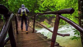 Tourist Walking On Bridge Hanging Above Rough. In the frame there is a back shot of a tourist with backpack walking along wooden bridge hanging above rough river stock footage