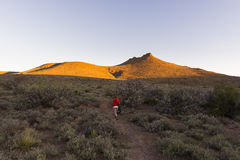 Tourist walking on marked trail in the Karoo National Park, South Africa. Scenic table mountains, canyons and cliffs at sunset. Ad Stock Images