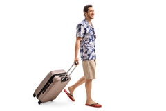 Tourist walking and pulling a suitcase. Full length profile shot of a tourist walking and pulling a suitcase isolated on white background.jpg Royalty Free Stock Image
