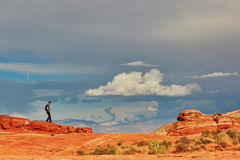 Tourist walking on red cliffs in Valley of the Fire national par Stock Photo