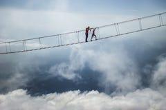 Tourist walking on rope bridge on the Mount Ai-Petri, Crimea. Tourist walks on a rope bridge on Mount Ai-Petri above abyss in Crimea. Man on a hanging bridge stock images
