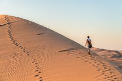 Tourist walking on the sand dunes at Sossusvlei, Namib desert, Namib Naukluft National Park, Namibia. Traveling people, adventure. And vacations in Africa Royalty Free Stock Photos