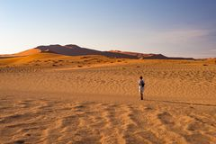 Tourist walking on the sand dunes at Sossusvlei, Namib desert, Namib Naukluft National Park, Namibia. Traveling people, adventure. And vacations in Africa Royalty Free Stock Image