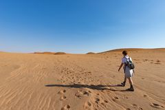 Tourist walking on the sand dunes at Sossusvlei, Namib desert, Namib Naukluft National Park, Namibia. Traveling people, adventure. And vacations in Africa Stock Image