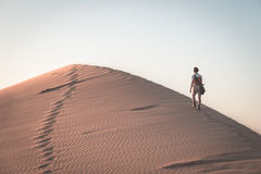 Tourist walking on the scenic dune 7 at Walvis Bay, Namib desert, Namib Naukluft National Park, Namibia. Afternoon light. Adventur Stock Photos