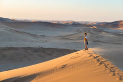 Tourist walking on the scenic dune 7 at Walvis Bay, Namib desert, Namib Naukluft National Park, Namibia. Afternoon light. Adventur Stock Image