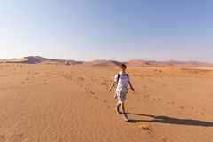 Tourist walking on the scenic dunes of Sossusvlei, Namib desert, Namib Naukluft National Park, Namibia. Adventure and exploration. In Africa Royalty Free Stock Photography