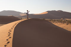 Tourist walking on the scenic dunes of Sossusvlei, Namib desert, Namib Naukluft National Park, Namibia. Adventure and exploration. In Africa Stock Photo