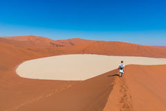 Tourist walking on the scenic dunes of Sossusvlei, Namib desert, Namib Naukluft National Park, Namibia. Adventure and exploration. In Africa Royalty Free Stock Photo