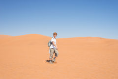 Tourist walking on the scenic dunes of Sossusvlei, Namib desert, Namib Naukluft National Park, Namibia. Afternoon light. Adventure. Tourist walking on the scenic Stock Photos