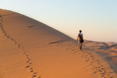Tourist walking on the scenic dunes of Sossusvlei, Namib desert, Namib Naukluft National Park, Namibia. Afternoon light. Adventure. And exploration in Africa stock photo