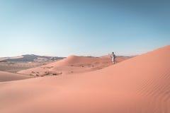 Tourist walking on the scenic dunes of Sossusvlei, Namib Naukluft National Park, Namibia. Adventure and exploration in Africa. Ton Stock Photo