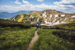 A tourist walks along a mountain meandering trail Royalty Free Stock Photo