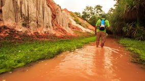 Tourist Walks along Red Waters of Fairy-Stream by Rocks Palms stock video