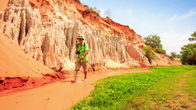Tourist Walks in Fairy-Stream Examines Bottom by Green Grass stock video