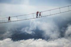 Tourist walking on rope bridge on the Mount Ai-Petri, Crimea. Tourist walks on a rope bridge on Mount Ai-Petri above abyss in Crimea. Man on a hanging bridge stock photos