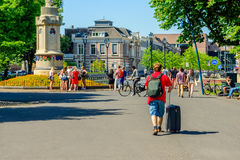 Tourist walks with trolley. BREDA, NETHERLANDS - MAY 25: An unidentified man walks with a trolley through the Valkenberg Park in Breda in the direction of the Royalty Free Stock Images