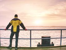 Tourist in warm clothes on sea mole at handrail. Man thinking. Tourist in warm clothes on sea mole at handrail. Autumn misty day. Tourist on pier in Dranske royalty free stock photos