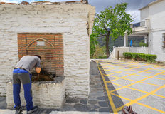 A tourist washes his face in the fountain of a small town. A tourist washes his face in the fountain of a small and rustic village Stock Photo
