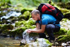 Tourist washing hands in a river Stock Images