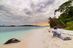 Tourist watching a relaxing sunset sitting on the beach in the remote Togean Islands, Central Sulawesi, Indonesia, upgrowing trave Stock Photo