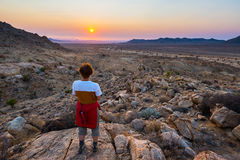 Tourist watching the stunning view of barren valley in the Namib desert, majestic visitor attraction in Namibia, Africa. Orange re Royalty Free Stock Photo