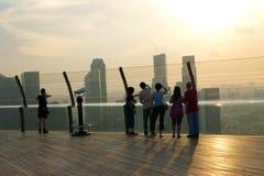 Tourist watching sunset against Singapore skyline Royalty Free Stock Photos