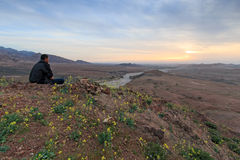 Tourist watching the sunset from the mountains in the Feynan natural Reserve in Jordan Royalty Free Stock Image