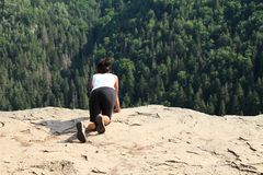 Tourist watching from Thomas´s View in Slovak Paradise. Indonesian tourist - scared young Papuan girl watching down from viewpoint Thomas´s View with sharp stock photography