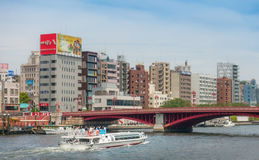 Tourist Water Bus is going under Asakusa red bridge. Tokyo, Japan - May 6, 2017: Tourist Water Bus is going under Asakusa red bridge Royalty Free Stock Image