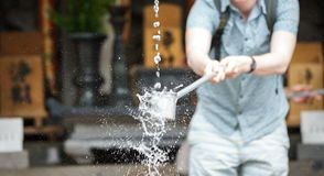 Tourist at water purification at entrance of Japanese temple. Foreign tourist takes water for purification at the entrance of Japanese temple Royalty Free Stock Image