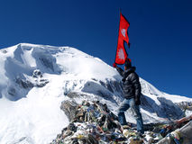 Tourist wavin Nepali Flag. A nepali tourist waving the flag of Nepal in the mountain in Thorong La Pass.Thorong La is the highest point on the Annapurna Circuit Stock Image