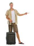 Tourist with wheels bag pointing on copy space Royalty Free Stock Image