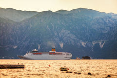 Tourist white cruise sea liner is sailing on the mountain backgr Stock Photos