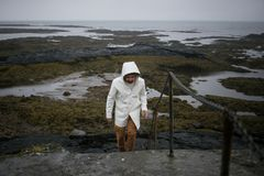 Tourist in white raincoat walks on iceland shore stock photography