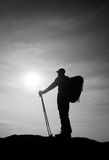 Tourist in windcheater with sporty trecking  poles in hands stand on rocky view point. Royalty Free Stock Photo